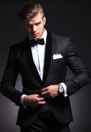 elegant young fashion man in tuxedo unbuttoning his jacket while looking at the camera.on black background photo