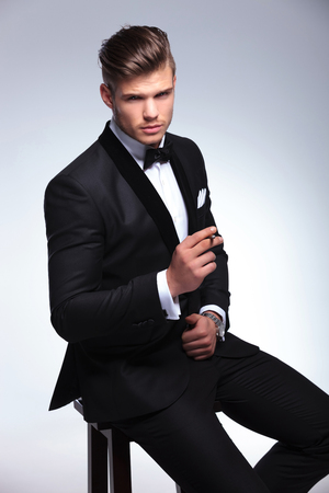seated elegant young fashion man in tuxedo holding a cigar in his hand while looking at the camera. on gray background photo