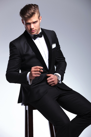 seated elegant young fashion man in tuxedo looking at the camera while holding a cigar between his fingers. on gray background photo