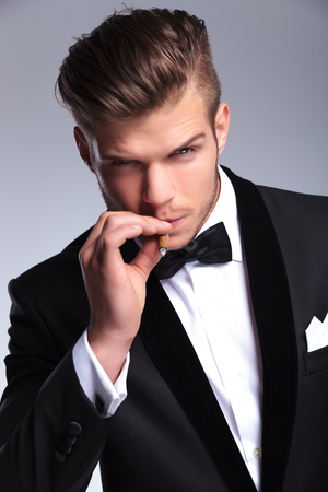 closeup portrait of an elegant young fashion man in tuxedo looking at the camera while taking a smoke from his cigar. on gray background photo