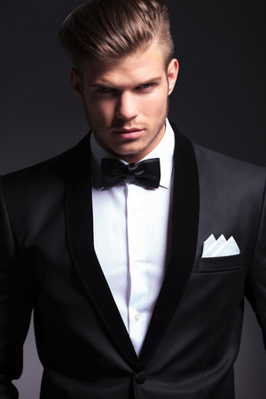 closeup portrait of an elegant young fashion man in tuxedo looking at the camera with a serious expression.on black background photo
