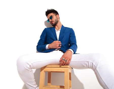tired elegant man wearing sunglasses is sitting on chair and holds the coats button or collar on white background