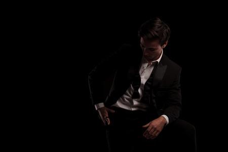 Hombre en esmoquin está mirando hacia abajo a su anillo sobre fondo negro Foto de archivo - 80997562