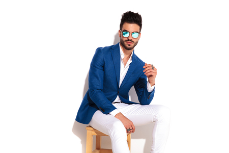 smiling elegant man in sunglasses sitting on chair on white background