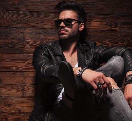 kant beeld van de mode man zit met gekruiste benen op houten achtergrond Stockfoto