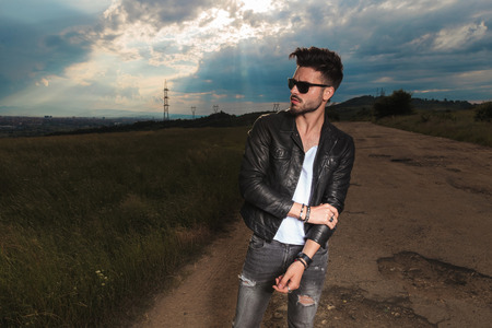 man in leather jacket and  sunglasses holds his elbow while standing to a side of a country road Stock Photo