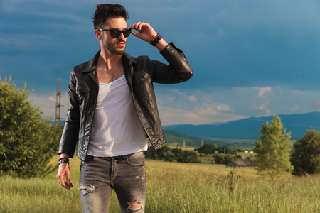 fashion man in leather jacket putting on his sunglasses and looks at the sunset in nature