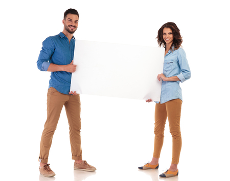 full body picture of smiling young couple holding blank board on white background