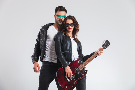 cool rock and roll couple with electric guitar on grey studio background Stock Photo