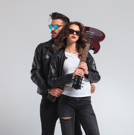 cool woman holding electric guitar on shoulder with man at her back; rock and roll couple posing in studio
