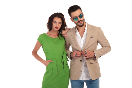 young modenr couple standing on white background; man wearing sunglasses buttoning his coat while his woman leans on his shoulder