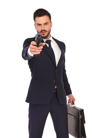 assasin: serious young hitman pointing and aiming his gun to the camera on white background Stock Photo