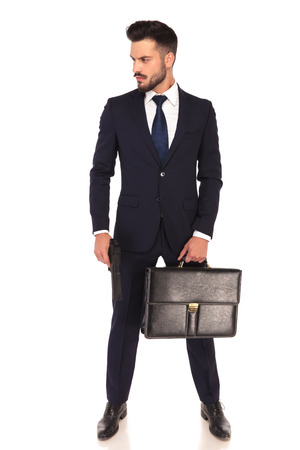 assasin: young assasin holding a gun and briefcase looks to side on white background Stock Photo