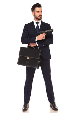 assasin: young modern hitman showing his gun while standing with suitcase on white background