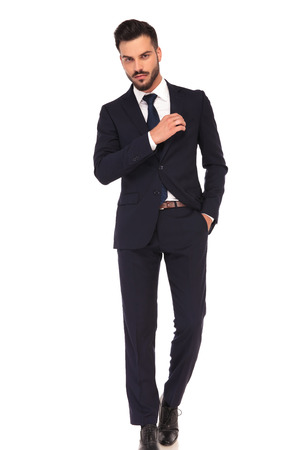 hands pocket: confident young business man fixing his chest pocket on white background