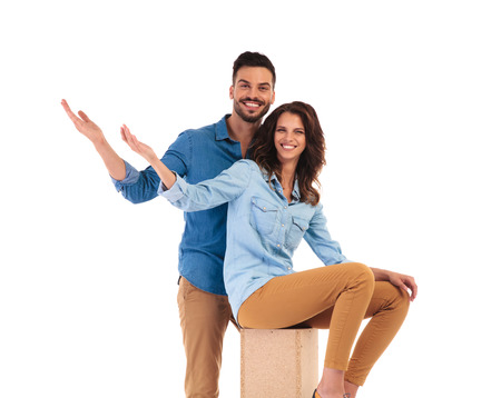 happy young casual couple welcoming you; woman in seated on wooden box and man is standing on white background