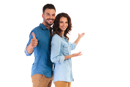 casual young couple presenting something and man makes the ok sign on white background