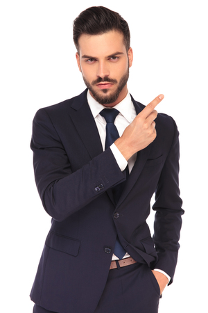 serious young business man snapping fingers or pointing on white background