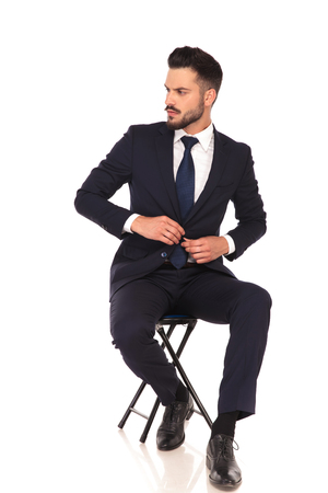 full body picture of a young business man sitting on chair and buttoning his suit on white background, looking to a side