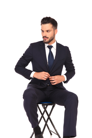 young business man closing his suit and looks to side while sitting on chair on white ebackground