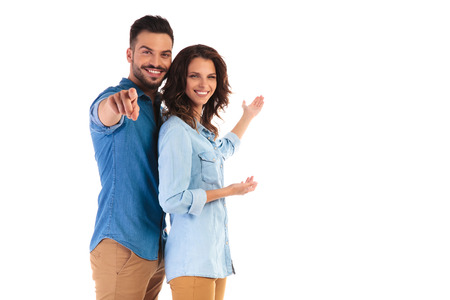 happy casual couple inviting you to something, presenting and pointing finger on white background