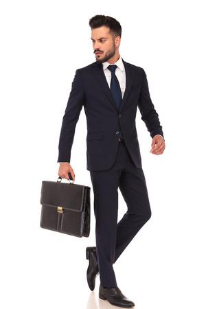 giovane uomo d'affari che trasportano valigetta sta camminando e guarda indietro sulla sua spalla su sfondo bianco Archivio Fotografico
