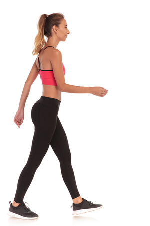 side view of a thin fitness young woman walking on white background Stock Photo