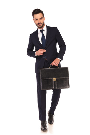 smiling modern business man walking with briefcase and holds button on the suit on white background