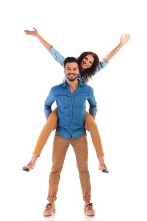 emocionado joven pareja casual de pie sobre fondo blanco, hombre llevando a la mujer mientras ella está con las manos en el aire Foto de archivo