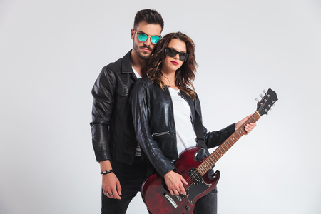 punk man behind his woman playing electric guitar on grey background