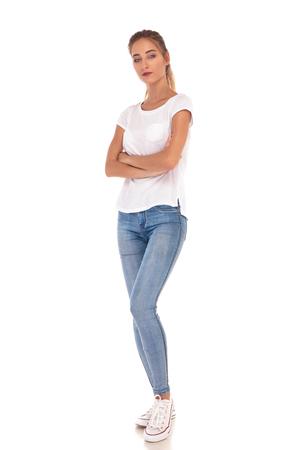 volledige lichaamsbeeld van een jonge toevallige vrouw die zich met handen bevindt die op witte achtergrond worden gekruist