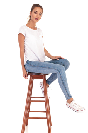 chairs: young blonde woman sitting on a stool on white background Stock Photo