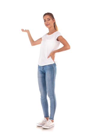 full body picture of a young casual woman presenting something on white background