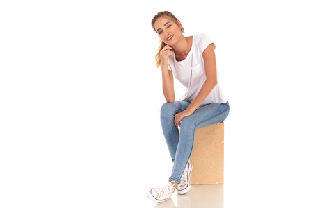 young blonde woman sitting on wooden box is laughing on white background Фото со стока