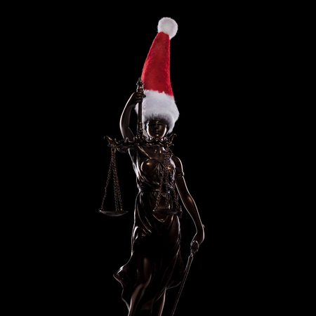 statue of the goddess of justice wearing santa claus hat on black background