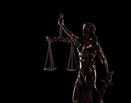 side view picture of goddess of justice statue on black background