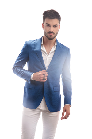 portrait of a young sexy man unbuttoning his coat on white background; picture with lights effects Stock Photo