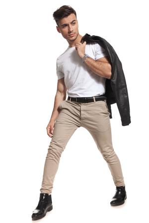 young man with leather jacket on shoulder looks to side while stepping on white background Stock Photo