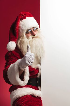 santa claus sitting near big blank board and makes ok sign on red background