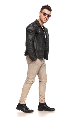 gelukkig lachend mode man lopen met handen in zijn zakken op een witte achtergrond Stockfoto