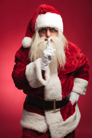 surprised santa claus standing with one hand on waist and makes the silence sign with finger covering mouth on red background Stock Photo