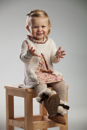 eager little girl is sitting on a chair on grey background Stock Photo