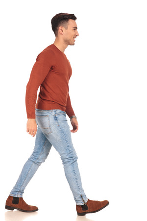 side view of a fit casual man walking on white background