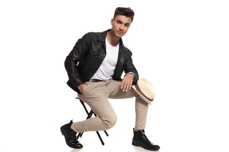 young casual man sitting on chair with hat on knee on white background