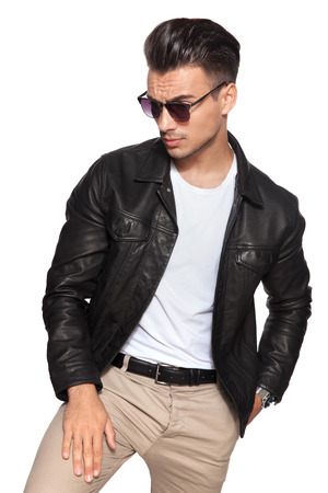 young sexy man looks down to a side on white background; he wears leather jacket and sunglasses