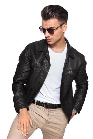 Joven sexy mira hacia un lado sobre fondo blanco; él usa chaqueta de cuero y lentes de sol Foto de archivo - 89817485