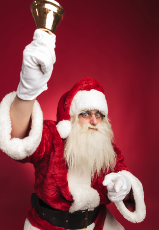 santa claus ringing bell and pointing finger on red background