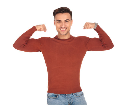 smiling young man flexing his biceps to show how strong he is on white background Stock Photo