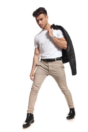 hot fashion man taking a big step forward with jacket on shoulder on white background Stock Photo