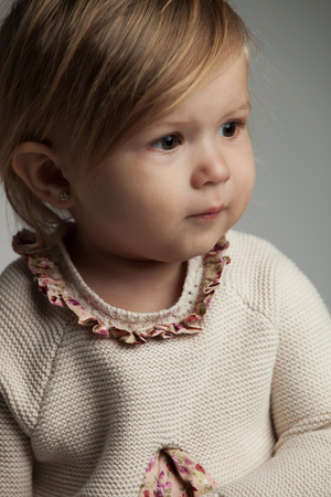 side portrait of a cute little girl wearing knitted dress and looks away on grey background Stock Photo